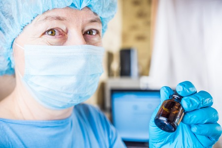 surgical cap: Female doctor wearing medical mask and surgical cap with medical vial in hands looking at patient and smiling Stock Photo