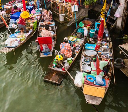 De boten van de kleurrijke handelaar in een drijvende markt in Thailand. Drijvende markten zijn een van de belangrijkste culturele toeristische bestemmingen in Azië. Stockfoto