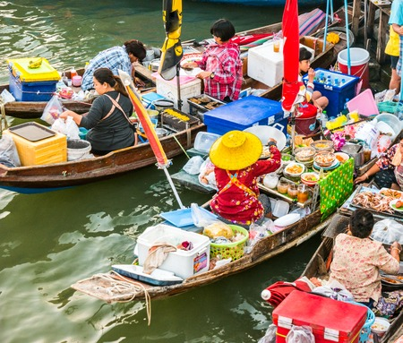 Colorful traders boats in a floating market in Thailand. Floating markets are one of the main cultural tourist destinations in Asia. Stock Photo