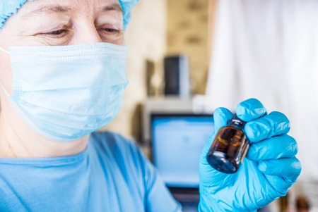 surgical cap: Female doctor wearing medical mask and surgical cap with medical vial in hands looking at the drugs and smiling