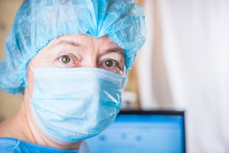 surgical cap: Female doctor wearing medical mask and surgical cap looking seriously and worried at patient with computer in background Stock Photo