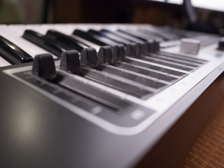 making music: Macro view of black professional digital musical piano synthesizer with sliders. Background image of recording studio equipment. DJ using electronical device for making music.