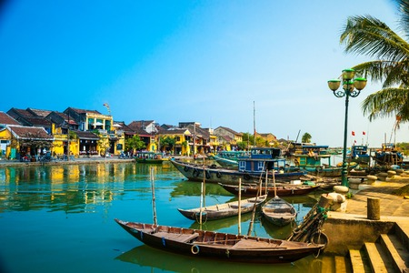 Traditional boats in front of ancient architecture in Hoi An, Vietnam. Hoi An is the World's Cultural heritage site, famous for mixed cultures & architecture. Reklamní fotografie - 53516167