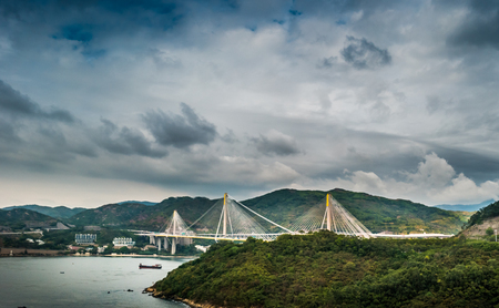 merging: Picturesque landscape with a view on Tsing Ma Bridge, Hong Kong, China. A view with urban and industrial merging with natural mountaings on islands and gorgeous clouds. Stock Photo