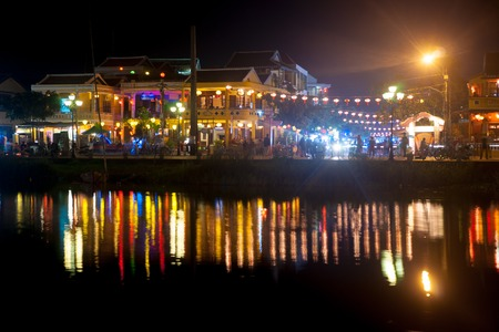 Night view of Hoi An town with light illumination and reflection in the river, Vietnam. Hoi An is the Worlds Cultural heritage site, famous for mixed cultures and architecture. Stock Photo