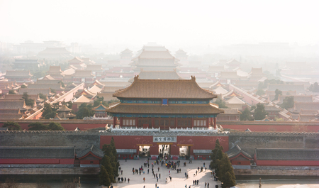An aerial bird view of the the famous Forbidden City in Beijing, China. The vast area of the architectural complex is covered with evening mist.
