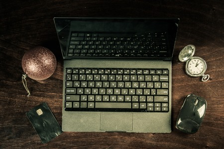 electronic banking: Black laptop on wood with christmas decoration, pocket watch and bank card viewed from above. Image for internet shopping, electronic banking and web payment. Stock Photo