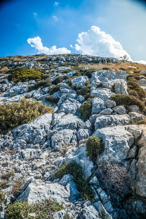 western part: Beautiful landscape with rocky mountains and clouds on the western part of Mallorca island, Spain.  Tramuntana mountains with green bushes. Tourist trekking destination in Spain. Stock Photo