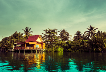 house float on water: Stilt houses built above river Mae Klong in Amphawa, rural Thailand. Beautiful countryside landscape at sunset.