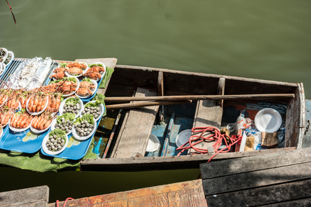 practised: Seafood on traders boats in a floating market in Thailand. Floating markets are one of the main cultural tourist destinations in Asia. Stock Photo