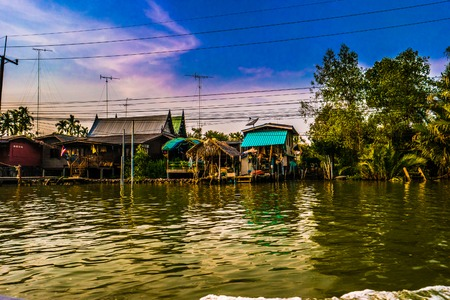 architecture bungalow: Stilt houses built above river Mae Klong in Amphawa, rural Thailand. Beautiful countryside landscape at sunset.