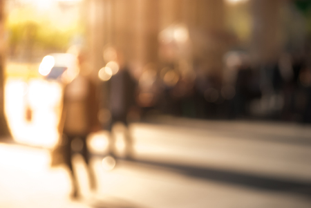 People walking down the street in the evening, beautiful light at sunset. The photo is purposely made out of focus, no faces are recognisible Stock Photo