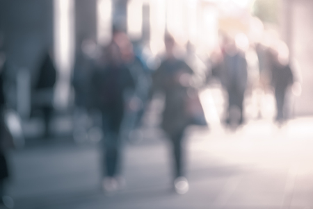 purposely: People walking down the street in the evening, beautiful light at sunset. The photo is purposely made out of focus, no faces are recognisible Stock Photo
