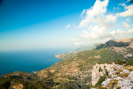 Beautiful landscape view of rocky mountains and clouds on the western part of Mallorca island, Spain. Tramuntana mountains with blue sea in background. Tourist trekking destination in Spain.