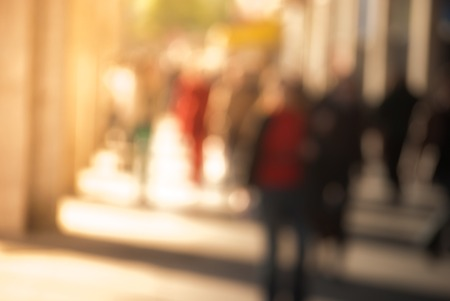 evening out: People walking down the street in the evening, beautiful light at sunset. The photo is purposely made out of focus, no faces are recognisible Stock Photo