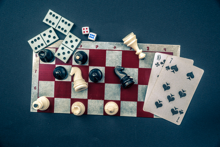 Various board games and figurines over checkers board and dark background. Metaphor for gaming and gambling. Imagens