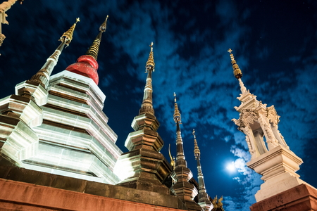 Night view of a temple in Chiang Mai, Thailand, with clouds flying in front of the moon. Standard-Bild