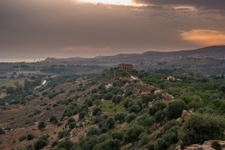 colonnade: Sunset in Valley of temples in Agrigento in Sicily with clouds and night illumination.