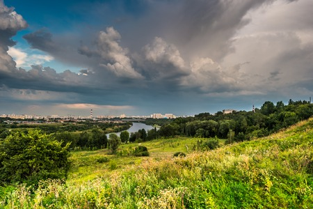 the great outdoors: Beautiful natural landscape at sunset with green grass, flowers and cloudy sky. City building in distance. Image of recreation in countryside. Great outdoors picture.