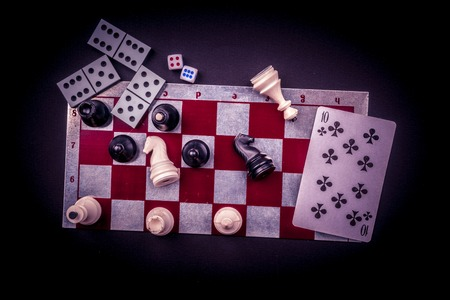 checkers: Various board games and figurines over checkers board and dark background. Metaphor for gaming and gambling. Stock Photo