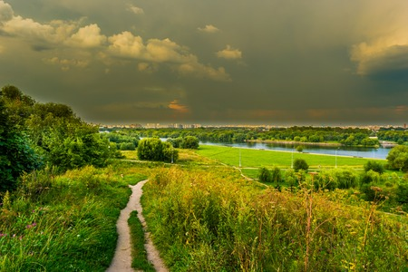 the great outdoors: Pathway on a hill with wildflowers. Beautiful natural landscape at sunset with green grass, flowers and cloudy sky. Image of travelling and adventure in countryside. Great outdoors picture.