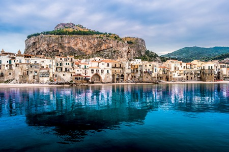 townscape: View on habour and old houses in Cefalu at sunset, Sicily. Beautiful townscape of old italian town. Travel photography. Stock Photo
