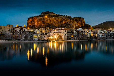 View on habour and old houses in Cefalu at night, Sicily. Beautiful townscape of old italian town. Travel photography. Stock Photo