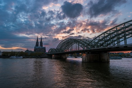 st german: Sunset view of Cologne Cathedral and Hohenzollern Bridge, Germany. Travel photo of Germany. Stock Photo