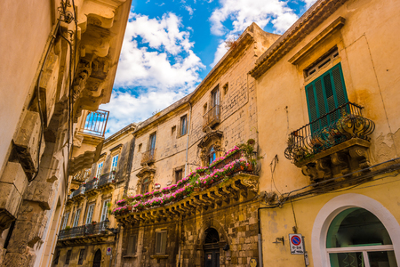 Baroque facede decorated with flowers in Italy. Beautiful travel photo. Colorful background texture with architecture and flowers. Stock Photo