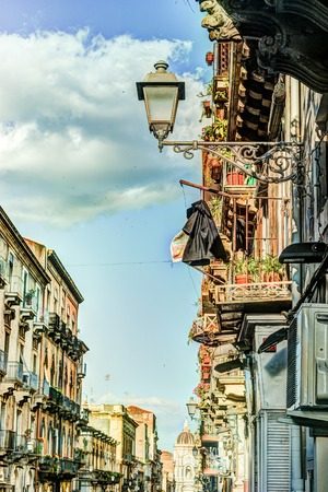 arhitecture: Catania arhitecture - Street view with facades of residential houses, lanterns and roofs in warm sunset light. Catania, Sicily, Italy.