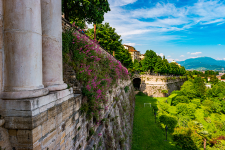 Panoramic view from Citta Alta, old town with columns of city gate and the wall of old castle covered with flowers. Bergamo, Lombardy, Italy Stock Photo
