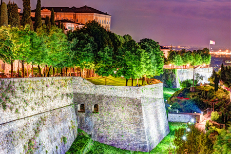 Stone walls of Castle La Rocca in Bergamo old town, Italy under the night lights.