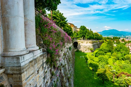 high section: Panoramic view from Citta Alta, old town with columns of city gate and the wall of old castle covered with flowers. Bergamo, Lombardy, Italy Stock Photo
