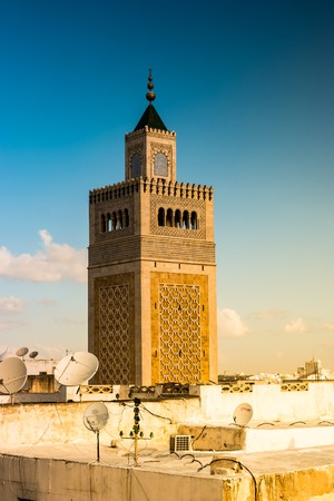 View of the Al-Zaytuna Mosque and the skyline of Tunis at dawn.