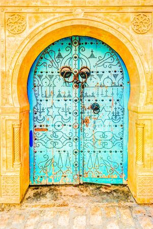 Traditional old painted door in a historical district or medina, Tunisia.