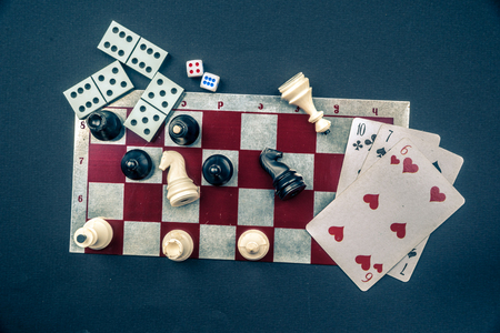 Various board games and figurines over checkers board Stock Photo