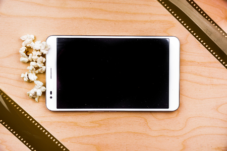 media gadget: Tablet pc on wood with attributes of cinema.
