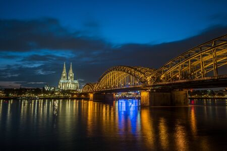 st german: Sunset view of Cologne Cathedral and Hohenzollern Bridge, Stock Photo