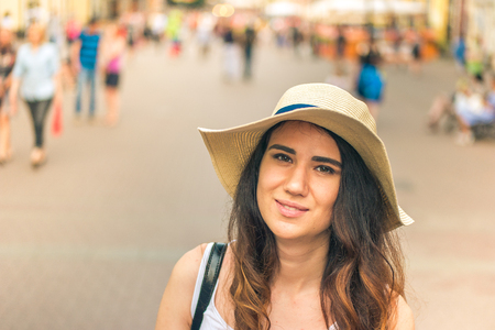 Girl with hat on summer day in the street.