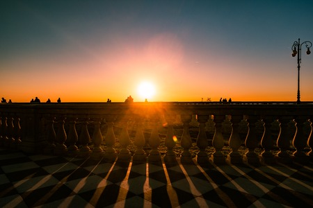 Leghorn (Livorno), Tuscany, Italy: promenade Mascagni Terrace at night, an elegant square on the coast with black and white checkered floor, columned bannister viewed against setting sun Stock Photo