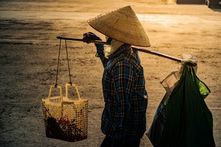 Vietnamese with conical hat carries a yoke on her shoulder along the street.