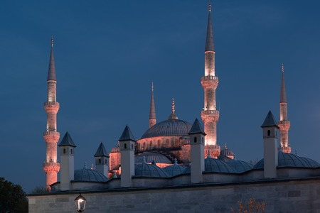 Blue Mosque at night with golden illumination, wide view of Istanbul in dusk.