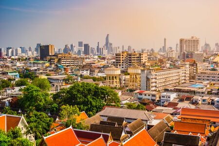 Aerial view of Bangkok monastery and modern office buildings, condominium in Bangkok city downtown with sunset sky, Bangkok , Thailand