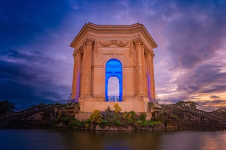 Bassin Principal de Peyrou marks end of the aqueduct in Montpellier, France. Beautiful picture of classical architecture at colorful sunset