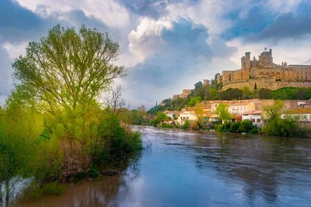 Panoramic view at the Old Bridge over Orb river with Cathedral of Saint Nazaire in Beziers Фото со стока