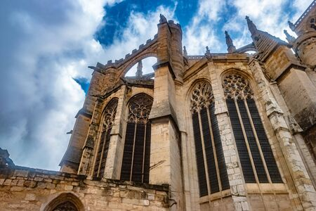 Gothic Cathedral of Narbonne seen from ground with dark architectural structures against sky and clouds, city in the south of France. Reklamní fotografie