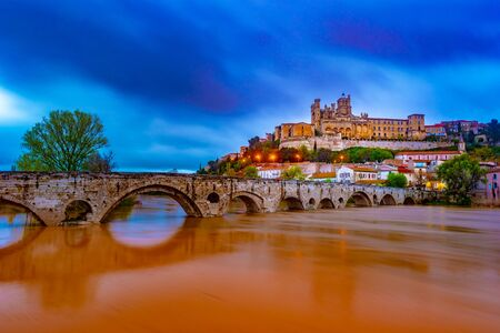 Cathedral and Pont Vieux at night. Beziers, southern France. Beautiful night illumination of medieval architecture.