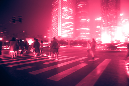 Perfect background image of blurred night street with unrecognizable people. Vintage looking image with washed out colors and red color cast