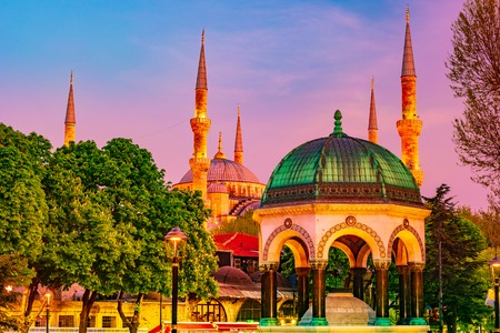 German fountain against Blue Mosque at night with golden illumination. Sultanahmet Camii mosque with six minarets - famous islamic monument of the Ottoman architecture in Turkey. Archivio Fotografico