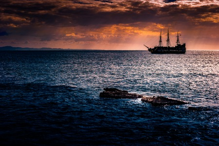 A lone ship against the morning sky. A distant historic ship in dramatic atmosphere.